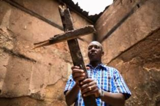 African Christian holds cross smaller
